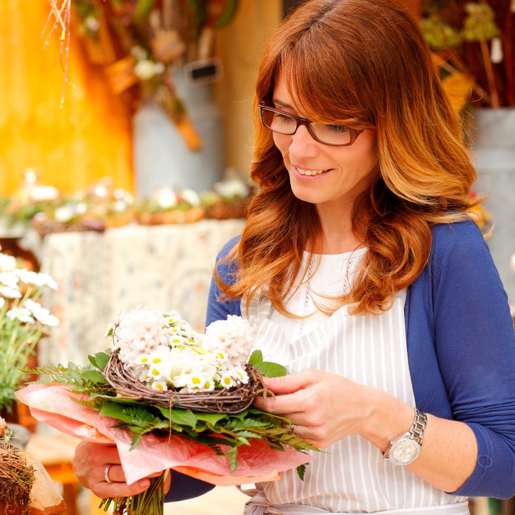 Woman holding and admiring an arrangement of flowers outside a store.